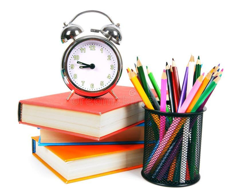 Libri, una sveglia e strumenti della scuola immagine stock libera da diritti