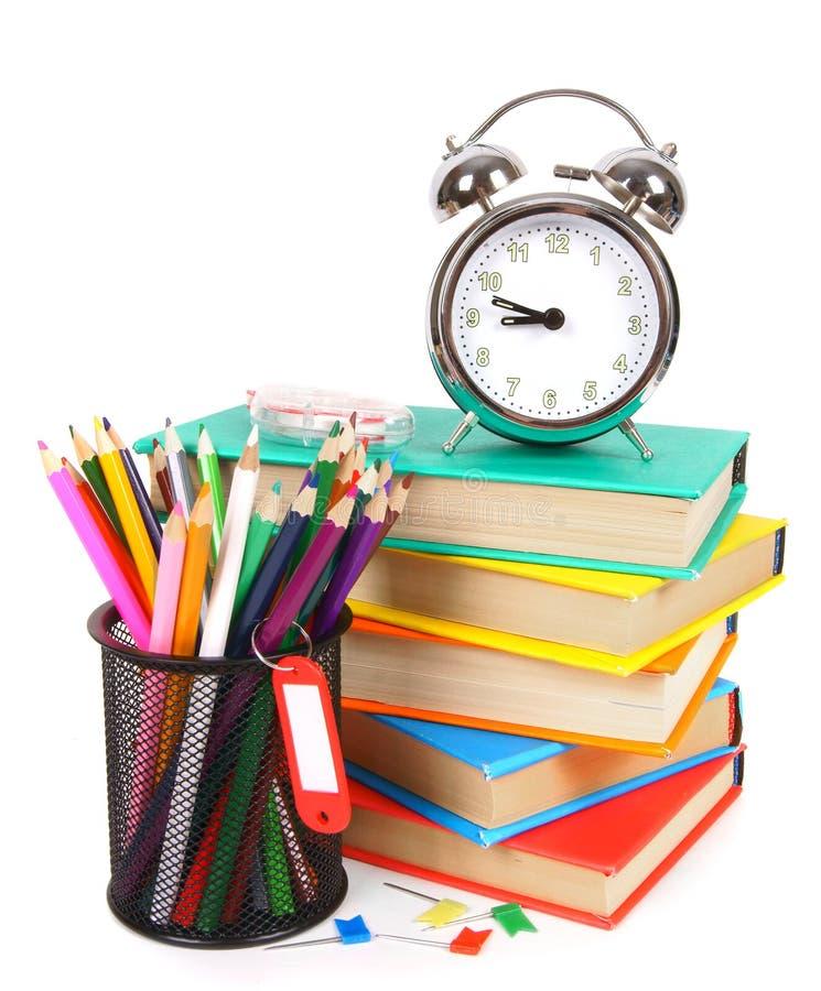 Libri, una sveglia e strumenti della scuola immagine stock