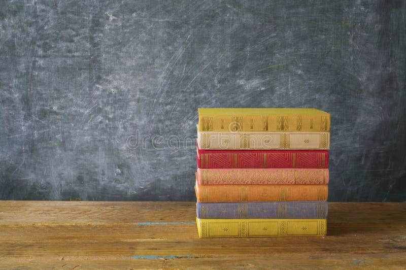 Libri variopinti davanti ad un bordo nero fotografia stock libera da diritti