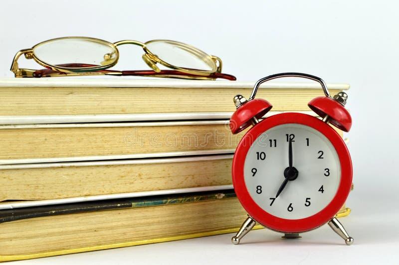 Libri, vetri e sveglia immagine stock