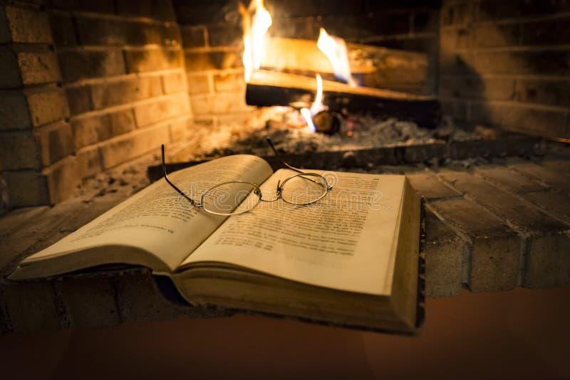 Libro abierto al lado de la chimenea ardiendo fotografía de archivo