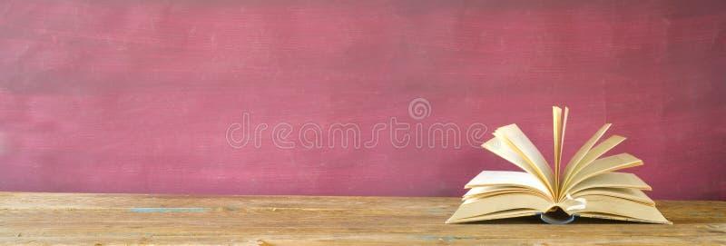 Libro abierto, cierre para arriba en el fondo sucio rojo, lectura, educación, literatura, aprendiendo, buen espacio de la copia fotografía de archivo libre de regalías