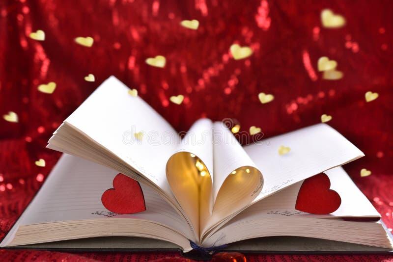 Libro abierto con las hojas de la forma de la forma del corazón para la tarjeta del día de San Valentín fotografía de archivo