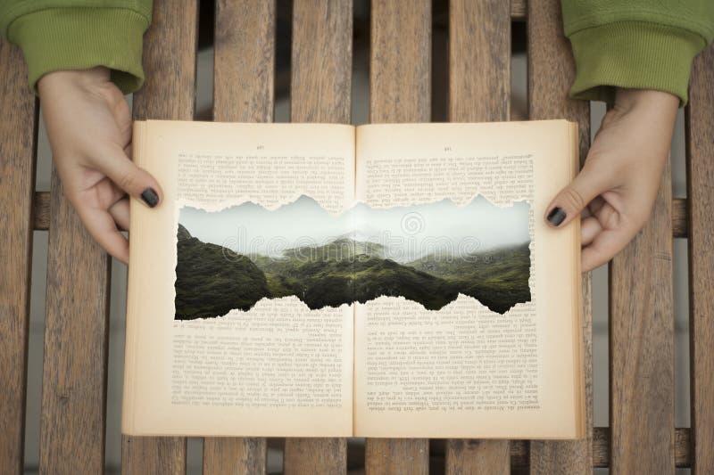 Libro abierto con una montaña exhausta imagenes de archivo