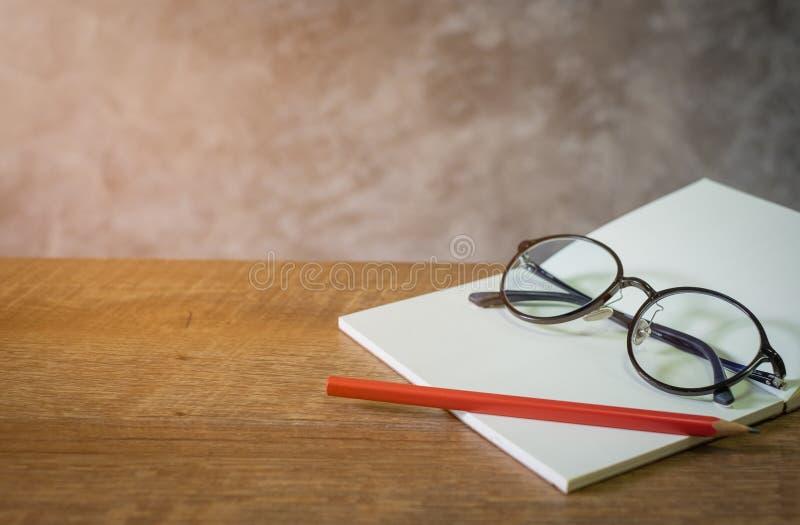Libro abierto en blanco con el lápiz y los vidrios rojos en la tabla de madera Cemente el fondo de la pared imagen de archivo libre de regalías