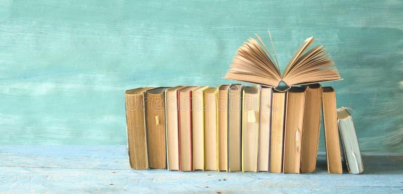 Libro abierto en una fila de libros viejos Leyendo, aprendiendo, educación, temas de la literatura foto de archivo