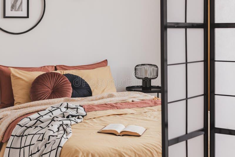 Libro abierto sobre edredones amarillos en el pequeño y acogedor interior de la habitación con acentos jengibre foto de archivo