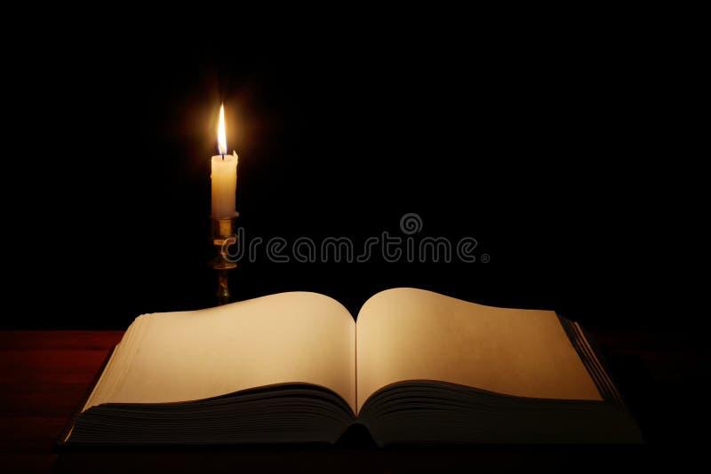 Libro abierto viejo con la vela ardiente imagen de archivo