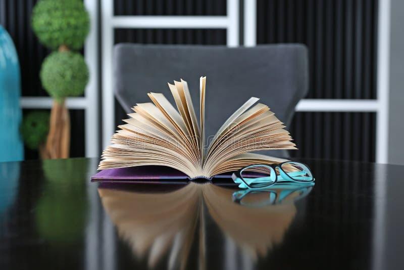 Libro abierto y gafas en mesa de madera. Fondo de la educaci?n fotos de archivo
