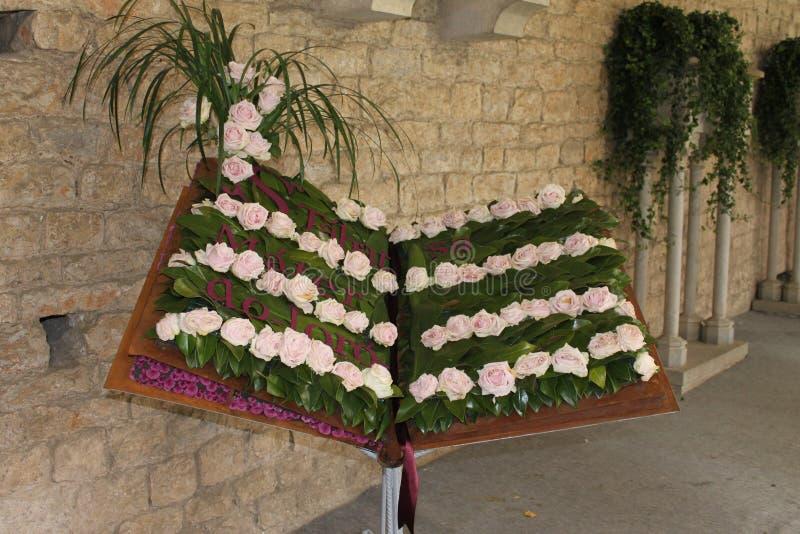 Libro adornado con las rosas con el texto de un canto gregoriano del aleluya imagen de archivo