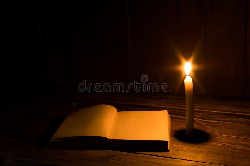 Libro antiguo viejo abierto con la vela ardiente Páginas en blanco foto de archivo