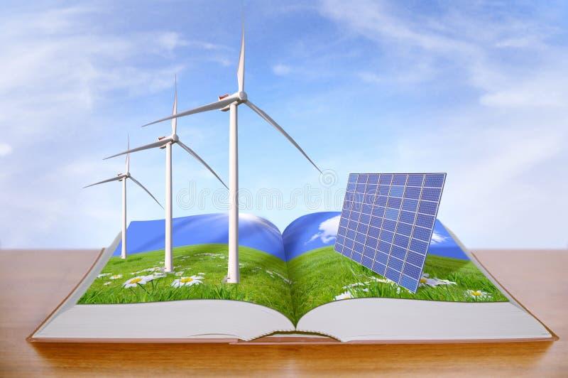 Libro aperto con i generatori eolici ed i pannelli solari fotografia stock