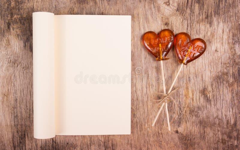 Libro aperto con la pagina in bianco e la lecca-lecca due sotto forma di un cuore su una vecchia tavola di legno immagine stock libera da diritti