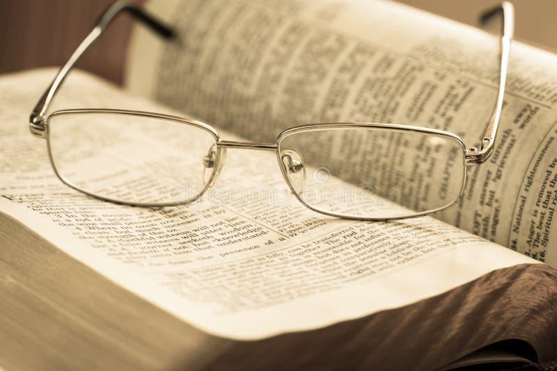 Libro aperto e vetri sulla tavola di legno immagini stock