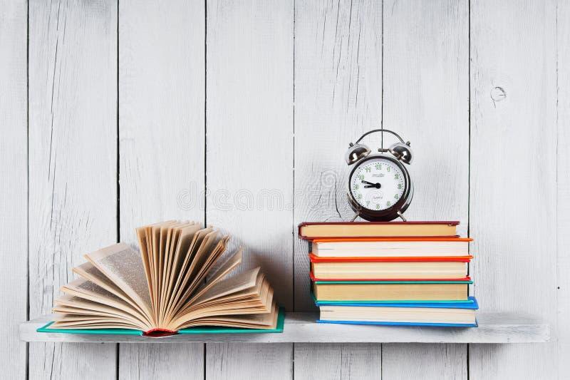 Libro aperto, libri multicolori e sveglia fotografie stock