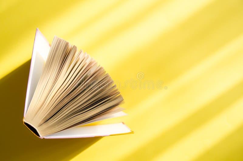 Libro aperto su un fondo giallo nel sole luminoso Il concetto di istruzione, la lettura, acquisto prenota Copi lo spazio fotografia stock libera da diritti