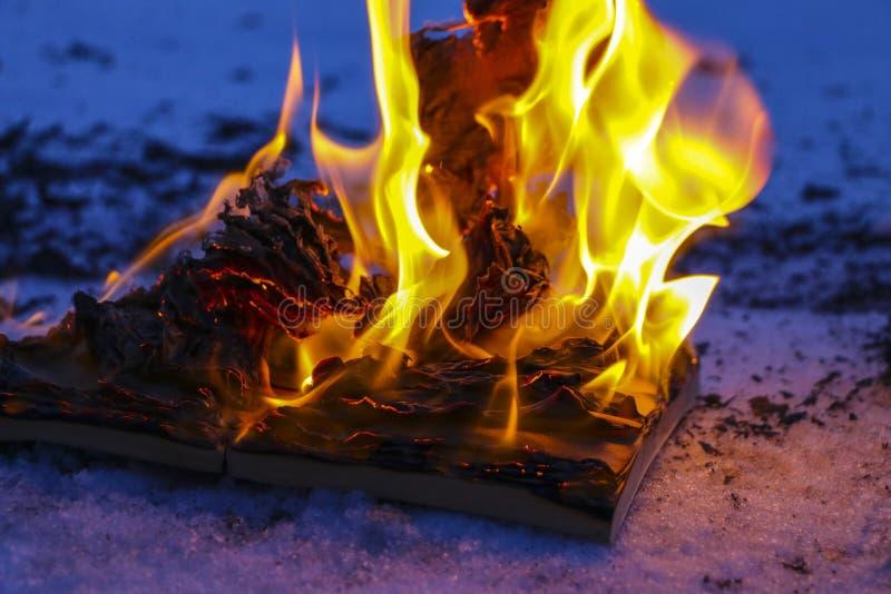 Libro ardiendo en nieve páginas con el texto en quemadura abierta del libro con la llama brillante fotos de archivo