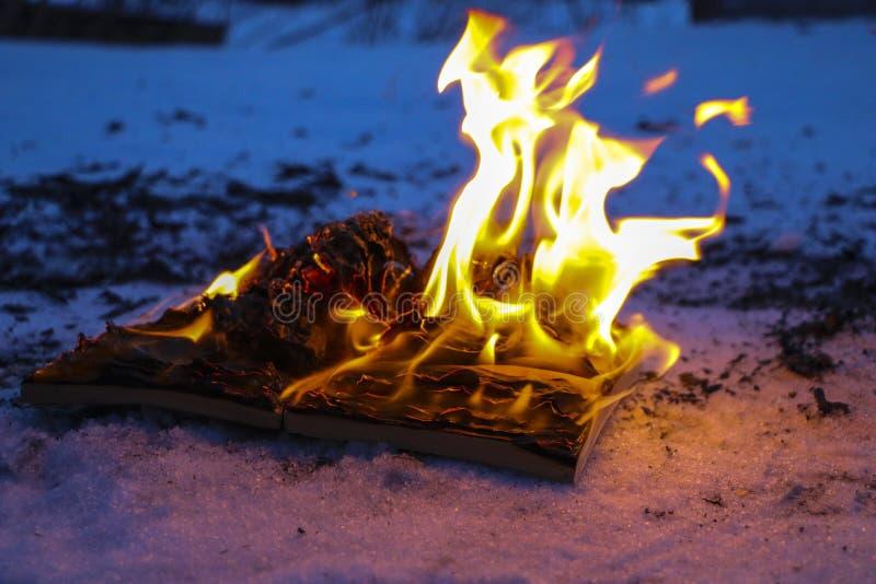 Libro ardiendo en nieve páginas con el texto en quemadura abierta del libro con la llama brillante imagen de archivo libre de regalías