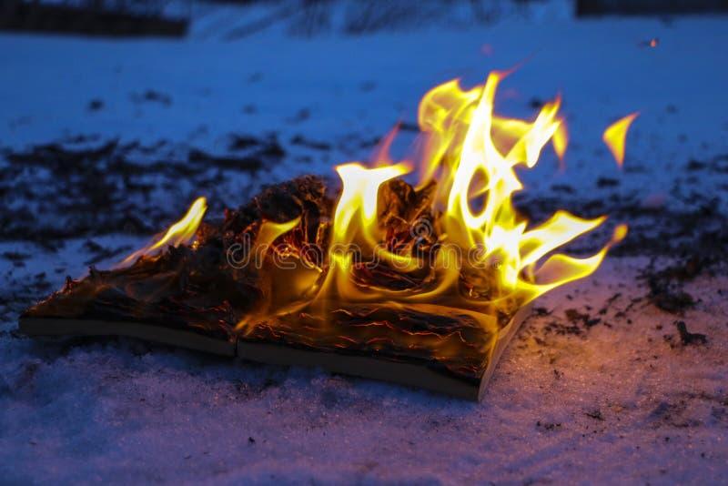 Libro ardiendo en nieve páginas con el texto en quemadura abierta del libro con la llama brillante imagenes de archivo