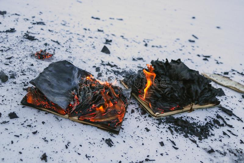 Libro ardiendo en nieve páginas con el texto en quemadura abierta del libro con la llama brillante imagen de archivo