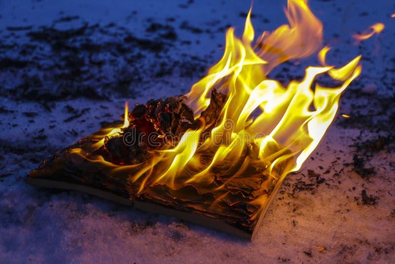 Libro ardiendo en nieve páginas con el texto en quemadura abierta del libro con la llama brillante fotografía de archivo