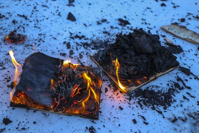 Libro ardiendo en nieve páginas con el texto en quemadura abierta del libro con la llama brillante foto de archivo libre de regalías