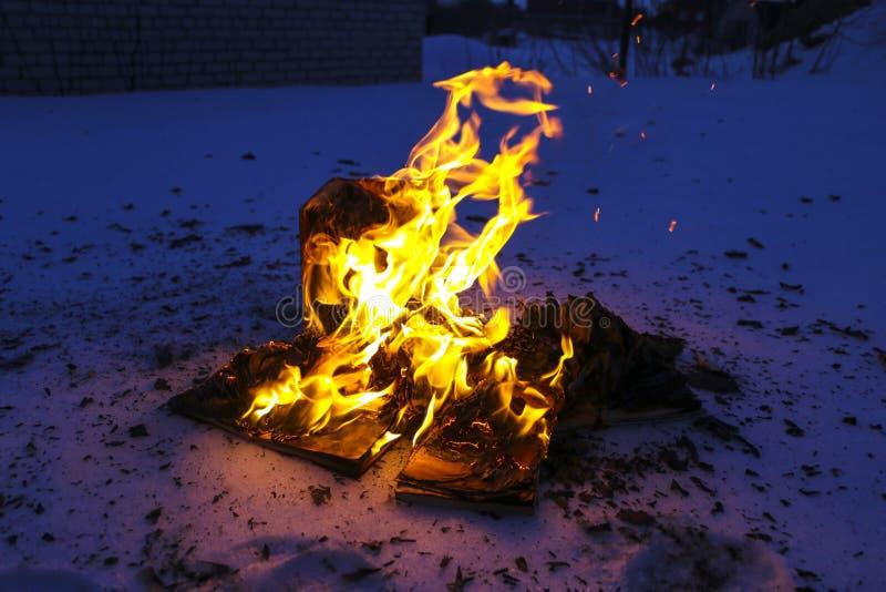 Libro ardiendo en nieve páginas con el texto en quemadura abierta del libro con la llama brillante fotografía de archivo libre de regalías