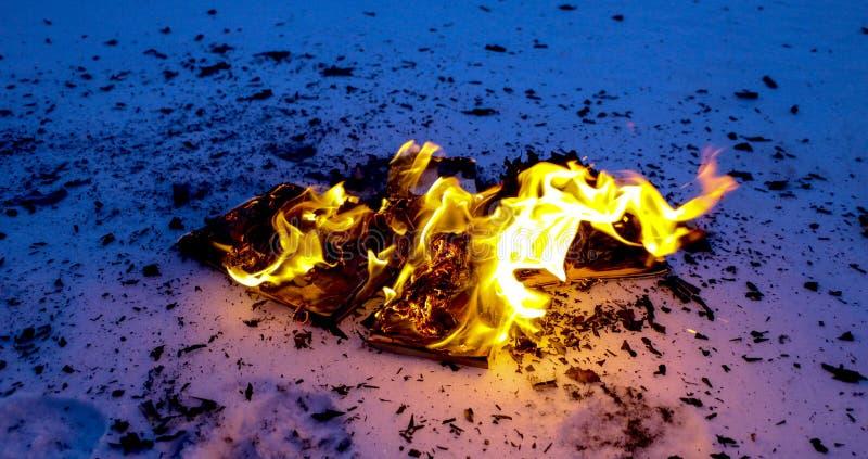 Libro ardiendo en nieve páginas con el texto en quemadura abierta del libro con la llama brillante fotos de archivo libres de regalías