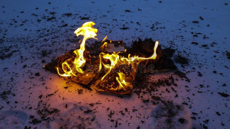 Libro ardiendo en nieve páginas con el texto en quemadura abierta del libro con la llama brillante foto de archivo