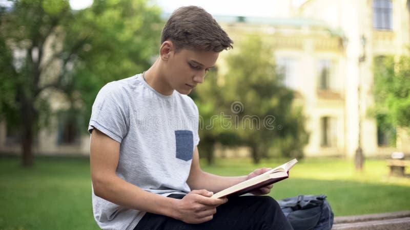 Libro atento de la aventura de la lectura del adolescente en banco en el parque, afici?n intelectual imagen de archivo