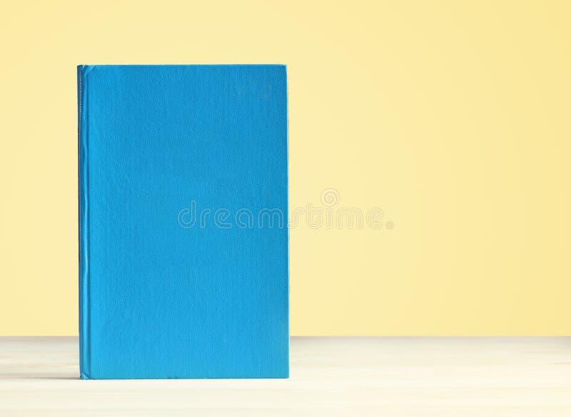 Libro azul en un fondo amarillo fotografía de archivo