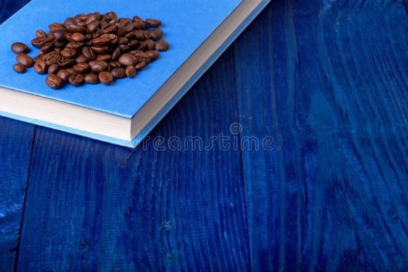 Libro azul y granos de café fotos de archivo libres de regalías