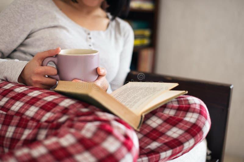 Libro bevente di lettura e del tè immagine stock