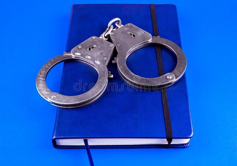 Libro blu e manette immagini stock libere da diritti