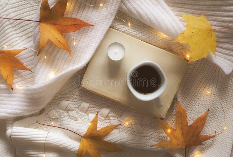 Libro, café, hojas de oro, vela y luces en un suéter blanco imagenes de archivo
