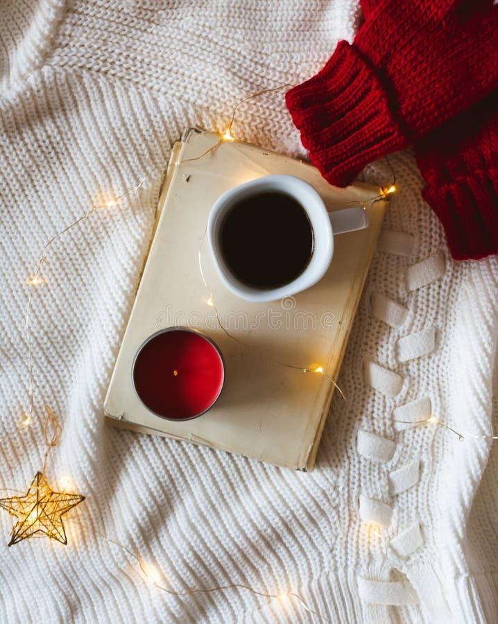 Libro, café, vela roja, manoplas rojas o guantes y luces de lana en un suéter blanco fotos de archivo