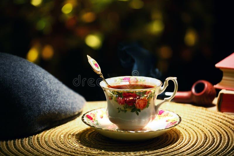 Libro caliente del tubo que fuma del sombrero del bokeh del oro de la taza de té nadie foto de archivo