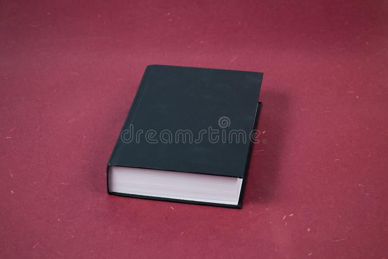 Libro cerrado del hardcover negro grande en fondo rojo fotografía de archivo libre de regalías