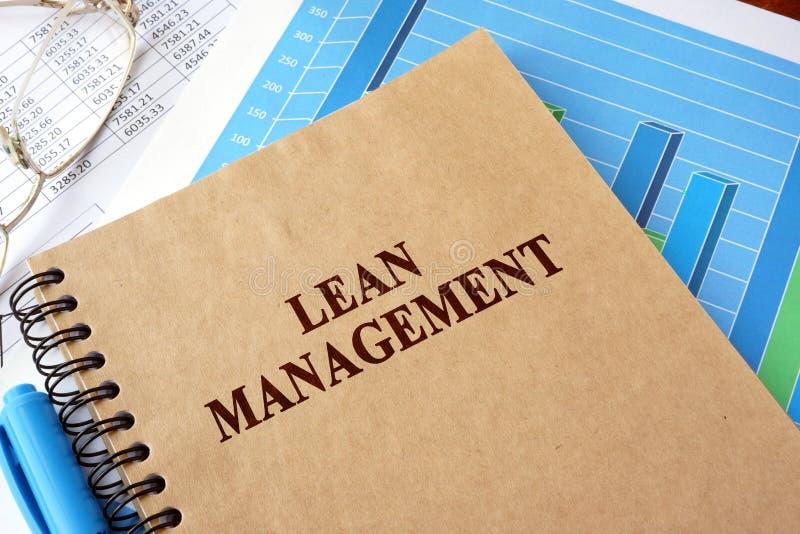 Libro con la gestión del magro del título en una tabla foto de archivo libre de regalías