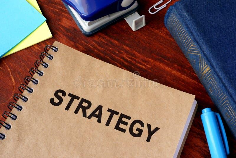 Libro con la strategia e le carte di titolo fotografia stock libera da diritti