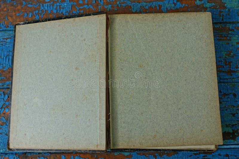 libro con le pagine grige che si trovano su una tavola blu immagine stock