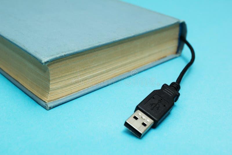 Libro con un conector para la conexión a un ordenador en un fondo azul imágenes de archivo libres de regalías
