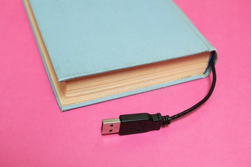Libro con un conector para la conexión a un ordenador en un fondo rosado imágenes de archivo libres de regalías