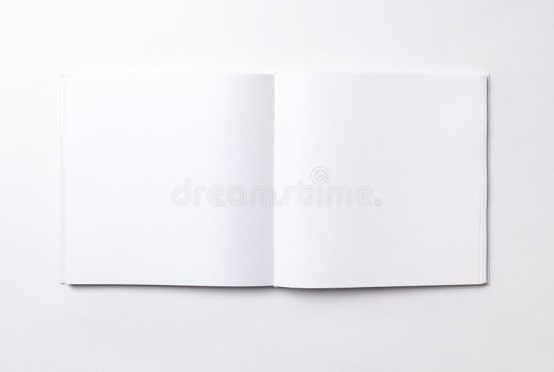 Libro cuadrado abierto en blanco, fondo blanco fotografía de archivo
