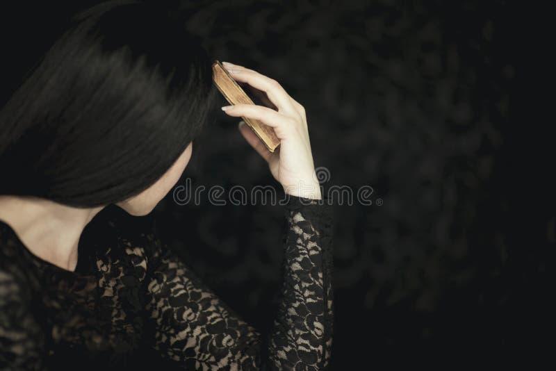 Libro d'annata al suo fronte, colpo rurale sensuale atmosferico molto scuro della bella tenuta della giovane donna vecchio dello  immagine stock libera da diritti