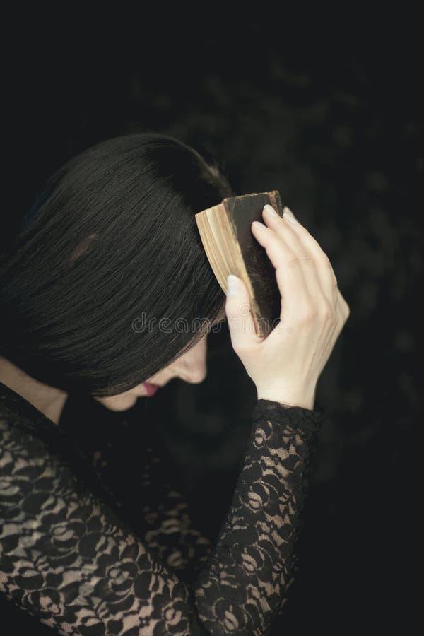 Libro d'annata al suo fronte, colpo rurale sensuale atmosferico molto scuro della bella tenuta della giovane donna vecchio dello  fotografia stock libera da diritti