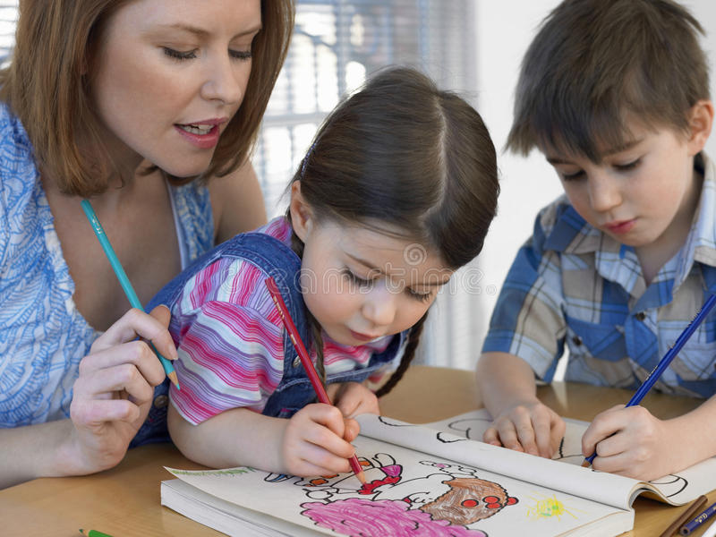 Libro da colorare dei bambini mentre madre che li assiste fotografie stock