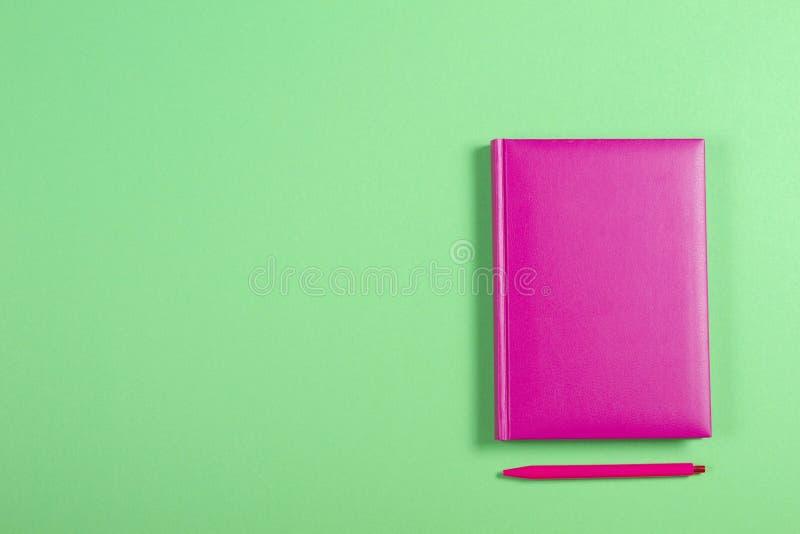 Libro dalla copertina rigida e penna rosa su fondo verde fotografia stock