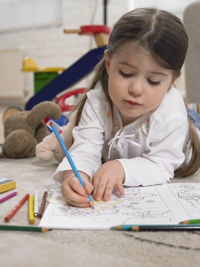 Libro de colorear de la niña en piso fotos de archivo