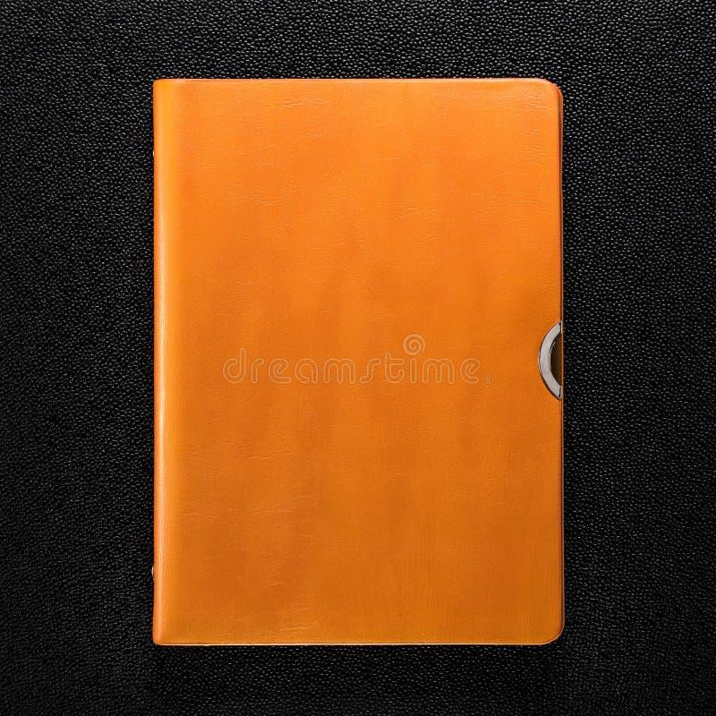 Libro de cuero anaranjado en fondo oscuro Vista delantera del libro de tapa dura imagen de archivo libre de regalías